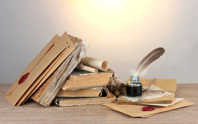 Vieux livres, défilements, crayon lecteur de clavette et encrier encastré images libres de droits