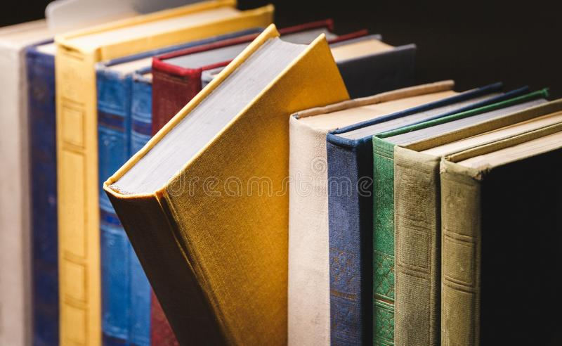 Vieux livres dans une rangée dans la bibliothèque de vintage sur la fin noire de fond image libre de droits