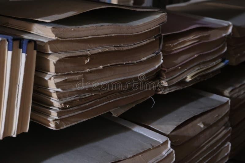 Vieux livres sur les étagères de la salle sombre d'archives de la bibliothèque Foyer s?lectif Lumière de sous-sol dans le dépôt d image libre de droits