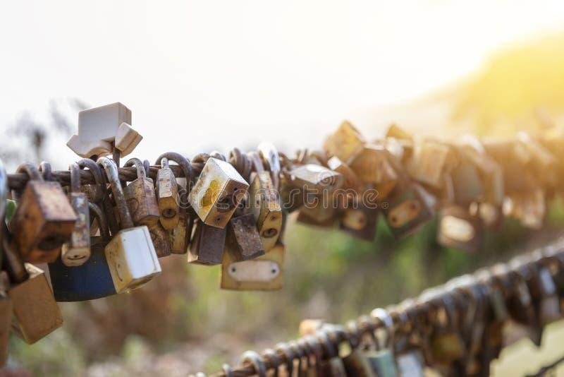 Vieux locksn rouillé en métal accrochant sur la barrière du pont au-dessus du fond brouillé de nature image libre de droits