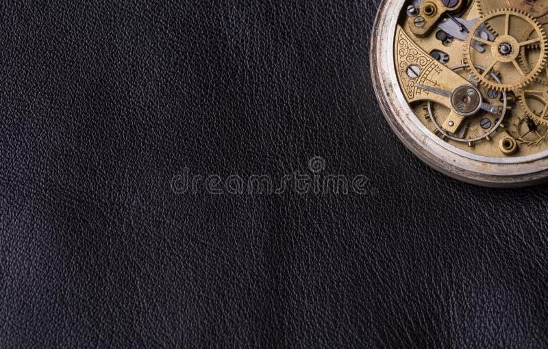 Vieux mécanisme d'horloge sur le fond en cuir noir image libre de droits