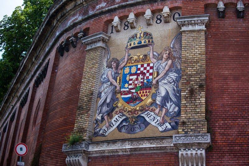 Vieux manteau de la Hongrie des bras sur un mur photographie stock