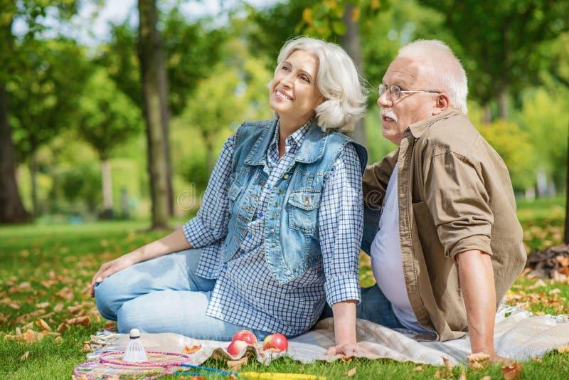 Vieux mari gai et épouse se reposant en parc photos stock