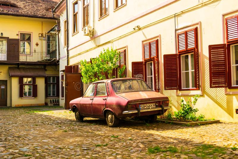 Vieux modèle de Dacia 1300, encore en service, garé dans une cour intérieure avec le pavé rond, au vieux centre de la ville de Si images stock