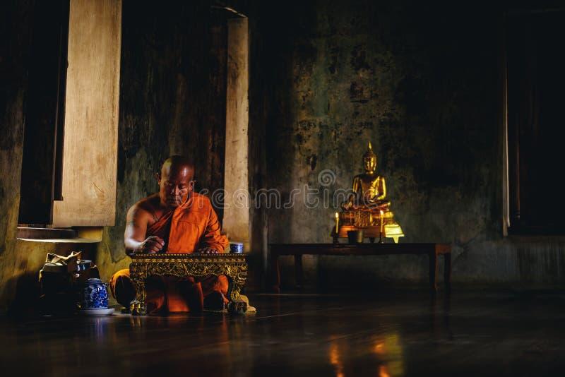 Vieux moine asiatique pensant pour écrire quelque chose au sanct d'Ayutthaya photos stock