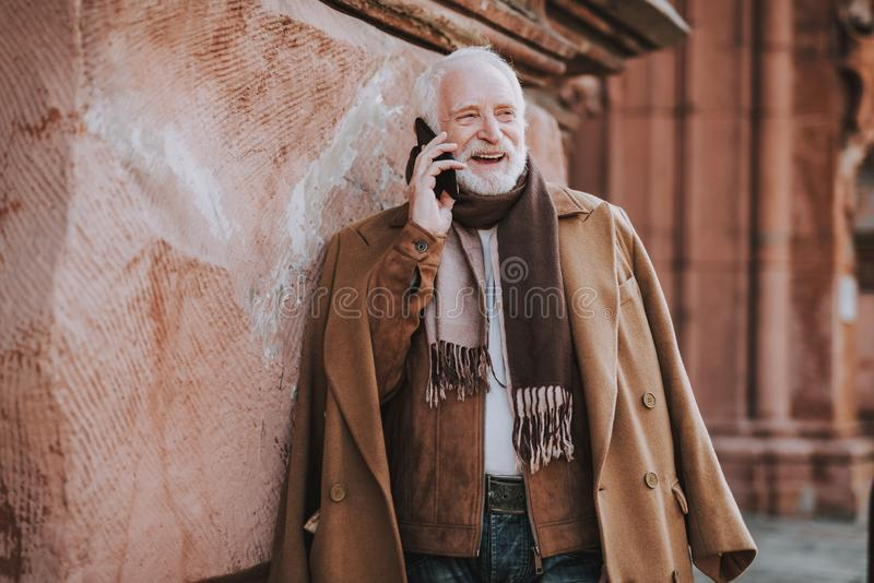 Vieux monsieur élégant parlant sur le téléphone portable sur la rue image stock