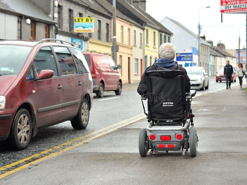 Vieux monsieur conduisant un fauteuil roulant électrique par le sentier piéton dedans photo stock