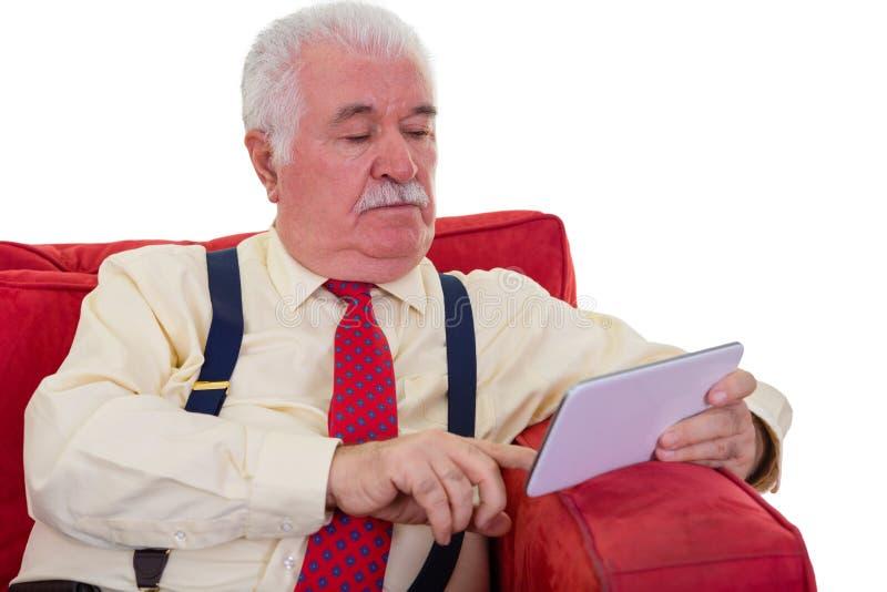 Vieux monsieur mis à jour avec la Tablette sur une chaise photographie stock libre de droits