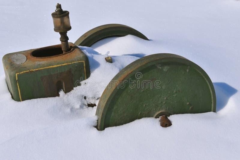 Vieux moteur à gaz enterré dans la neige après une tempête de neige image libre de droits
