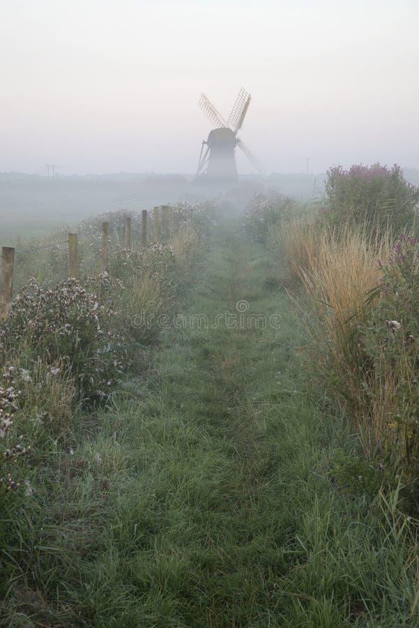 Vieux moulin à vent dans le paysage brumeux de campagne en Angleterre image libre de droits