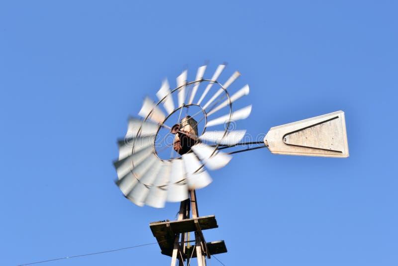 Vieux moulin à vent en fonction dans un jour bleu image libre de droits