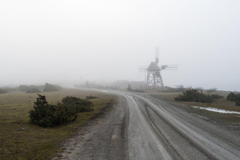 Vieux moulin à vent par le bord de la route dans la brume photo stock
