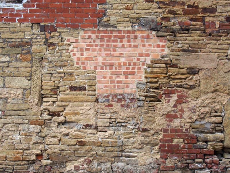 Vieux mur beaucoup réparé et raccordé fou des types mélangés des briques et de pierres photo stock