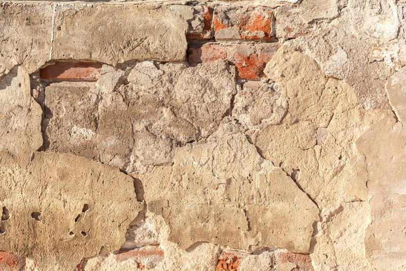 Vieux mur criqué et ruiné fait de briques rouges avec des restes de plâtre Stuc grunge de fond sur un vieux mur de briques photographie stock