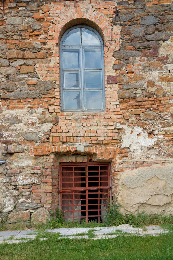 Vieux mur de briques orange avec des hublots image stock
