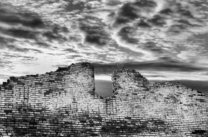 Vieux mur de briques ruiné contre le ciel sombre images stock