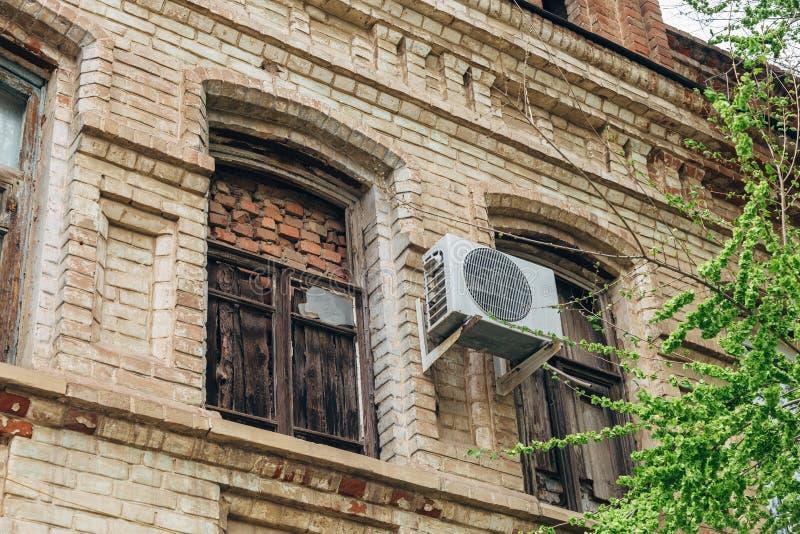 Vieux mur de construction avec la climatisation et avec étendu et embarqué vers le haut des fenêtres photographie stock libre de droits