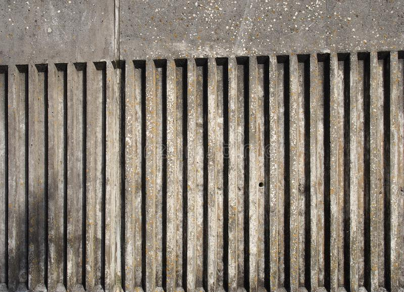 Vieux mur en béton extérieur souillé avec la conception cannelée de rayure verticale avec une texture moulée approximative avec l images libres de droits