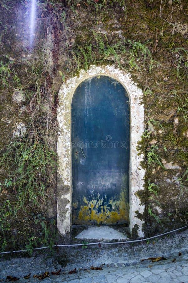 Vieux mur en pierre couvert de la mousse et de vieille porte rouillée photographie stock libre de droits