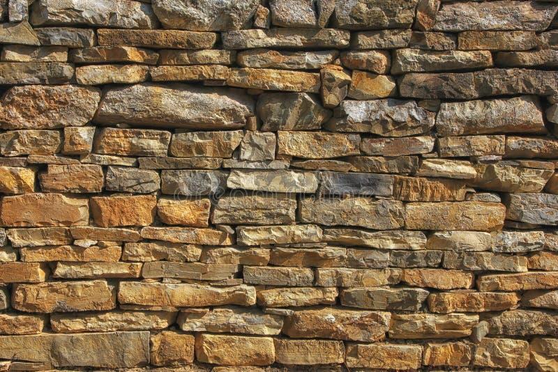 Vieux mur en pierre superficiel par les agents photographie stock libre de droits