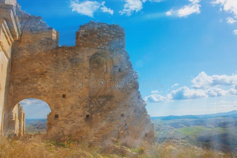 Vieux mur ruiné contre le ciel bleu et la lumière du soleil lumineuse dans Craco, Italie photo stock