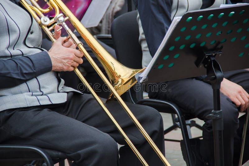Vieux musican habillé dans le men& x27 ; gilet classique de s jouant sur un trombone dans un orchestre, support de musique derriè photos stock