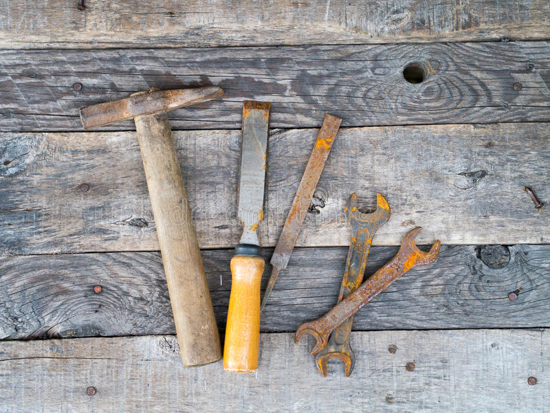 Vieux outils rouillés de vintage sur le fond en bois gris superficiel par les agents photos libres de droits