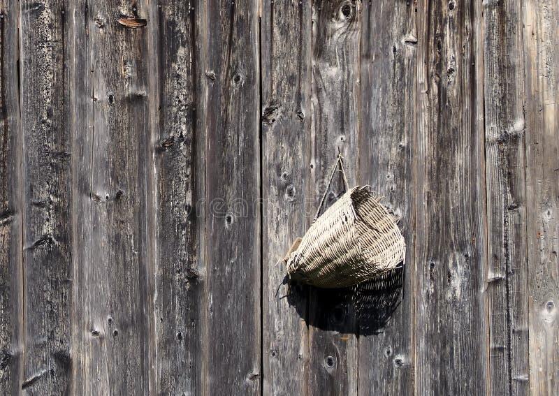 Vieux panier en osier accrochant sur un mur en bois rustique superficiel par les agents fond pour l'espace de copie images stock