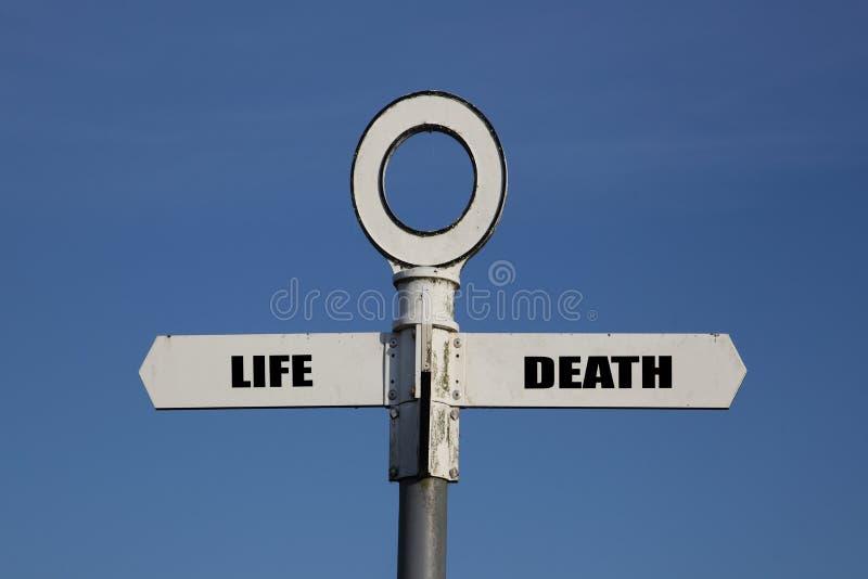Vieux panneau routier avec la vie et mort se dirigeant dans des directions opposées image libre de droits