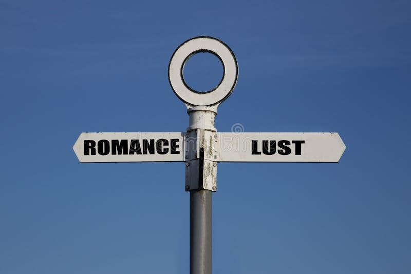 Vieux panneau routier avec le romance et convoitise se dirigeant dans des directions opposées photographie stock libre de droits