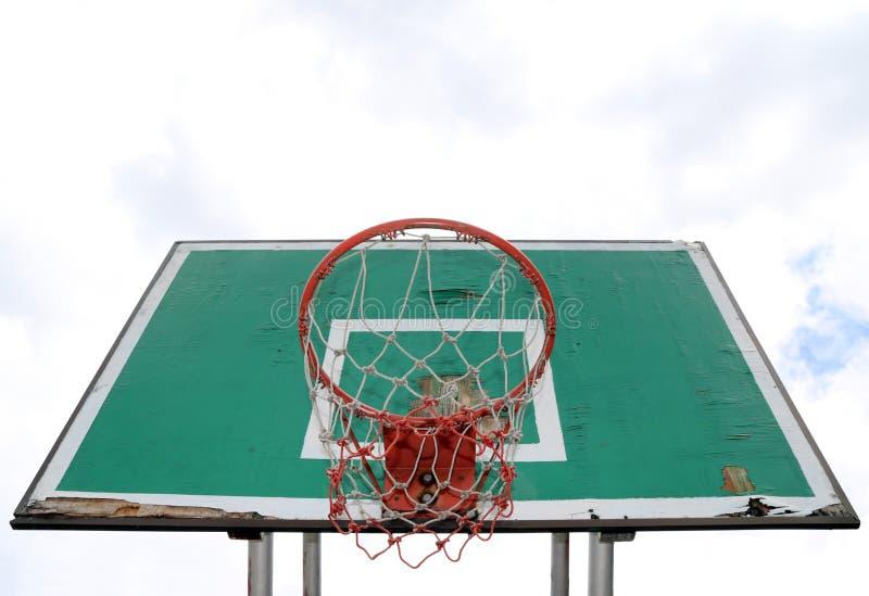 Vieux panneau vert de basket-ball avec le cercle rouge et de maille blanc-rouge sur le fond blanc de ciel photos libres de droits