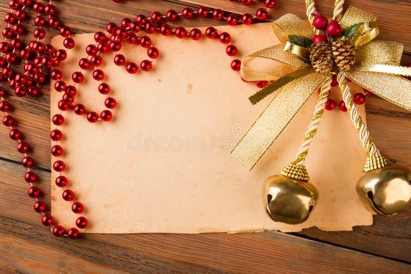 Vieux papier avec les perles et les cloches de Noël rouges photo stock