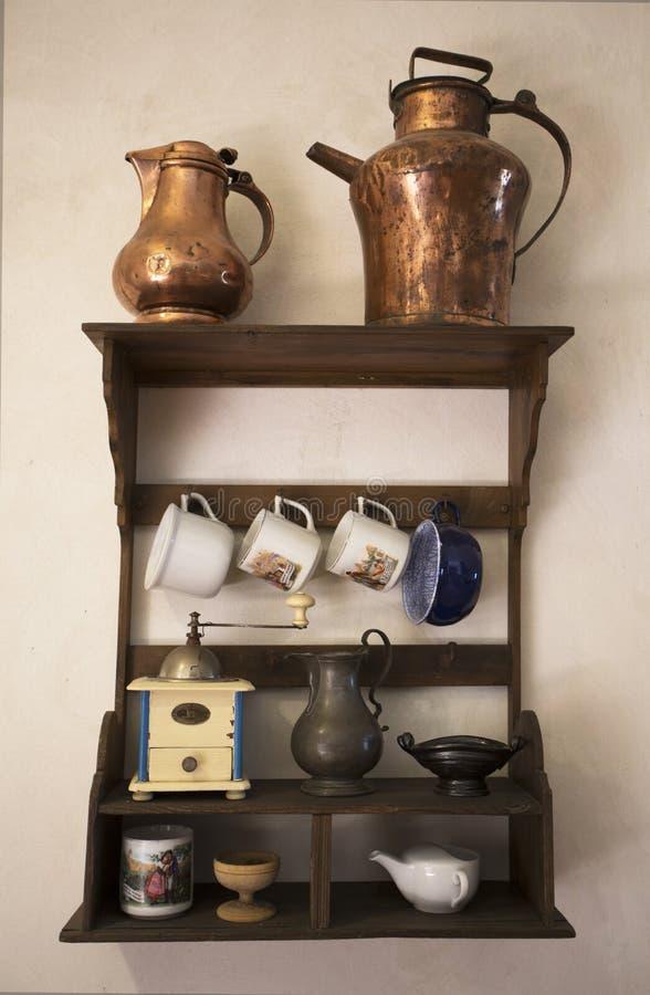 Vieux paraboloïdes Cookware historique Vieux hunged sur l'étagère en bois sur le mur médiéval photos libres de droits