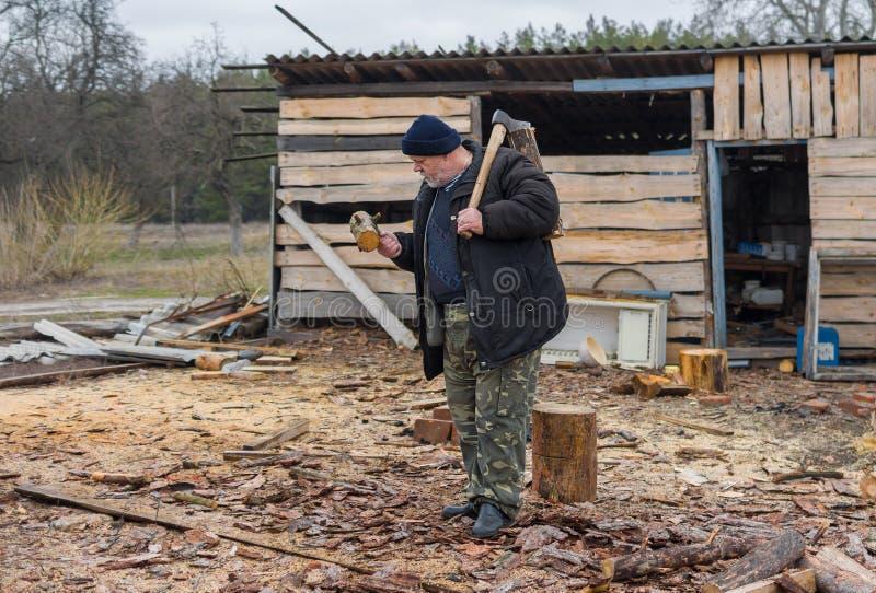 Vieux paysan ukrainien avec une hache photographie stock