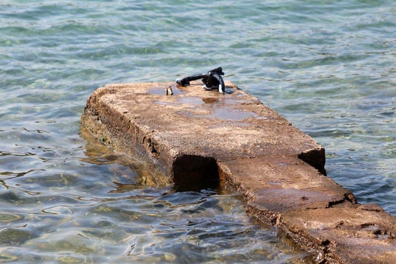 Vieux petit pilier concret rocheux improvisé entouré avec la mer calme claire avec le demi masque et la prise d'air de plongée photo stock
