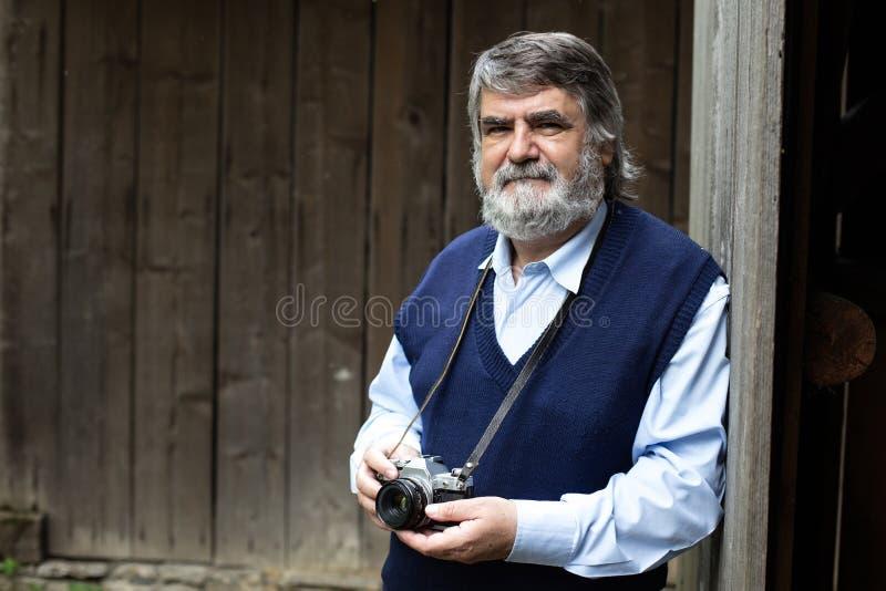Vieux photographe se tenant sur le fond en bois image libre de droits