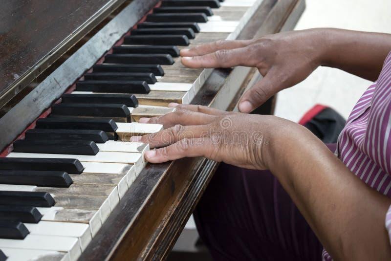 Vieux piano brun public avec la main masculine noire jouant là-dessus photographie stock
