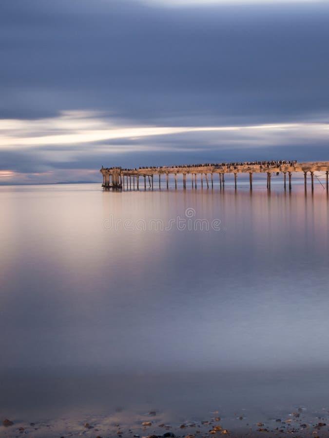Vieux pilier en bois décomposé à Punta Arenas, vieux dock au Chili sur l'océan pacifique Coucher du soleil image stock