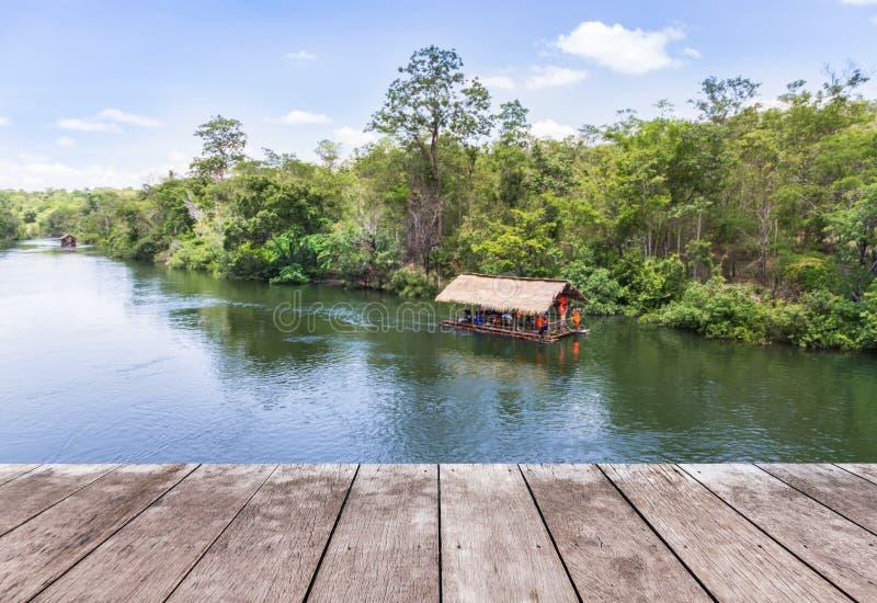 Vieux plancher en bois de terrasse de balcon avec la hutte en bambou de radeau flottant en rivière images stock