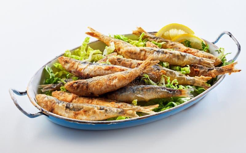 Vieux plat de vintage avec les sardines frites dans la pâte lisse images stock