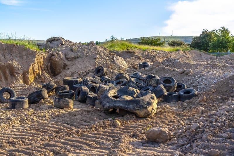 Vieux pneus en caoutchouc noirs jetés au sol sec avec des voies de pneu images stock