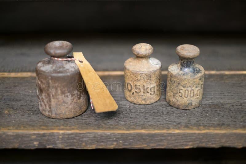 Vieux poids sur le banc de travail - poids de kilogramme de vintage sur le backgr en bois images libres de droits