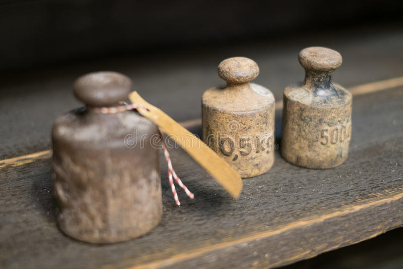 Vieux poids sur le banc de travail - poids de kilogramme de vintage sur le backgr en bois photo stock