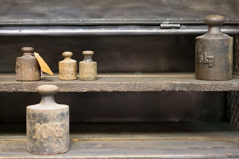 Vieux poids sur le banc de travail - poids de kilogramme de vintage sur le backgr en bois photos libres de droits