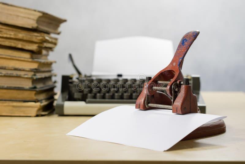 Vieux poinçon de papier de bureau sur une table en bois Accessoires de bureau dessus photos stock