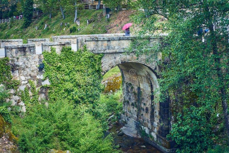 Vieux pont de roche croisant un courant, avec la personne flânant avec un parapluie rouge photo stock