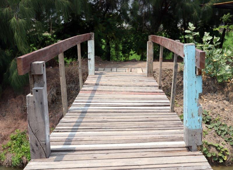 Vieux pont en bois croisant le ruisseau et le fond le TR vert photographie stock
