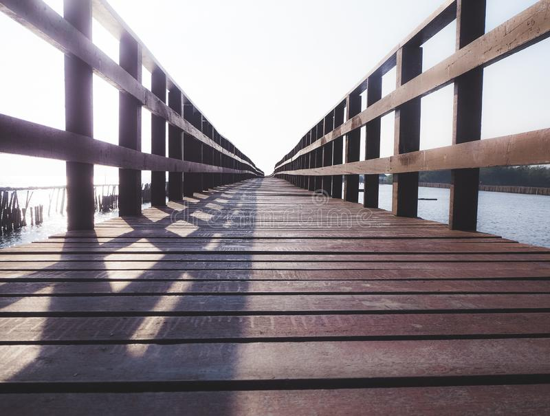 Vieux pont en bois de pied avec des balustrades au-dessus de la mer photographie stock libre de droits