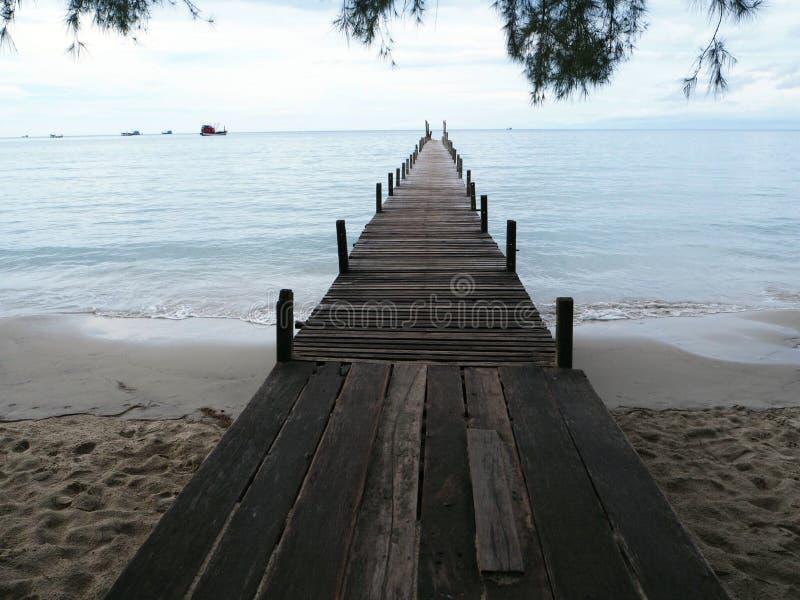 Vieux pont en bois vers la mer dans l'avant de plage le soir photos libres de droits