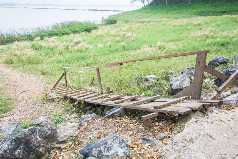 Vieux pont en bois vers le bas à l'herbe de champ près du reservior photographie stock libre de droits